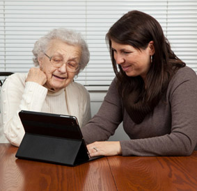 Senior Playing Game with Touch Screen Tablet PC